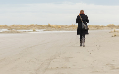 Lonely woman walking on a beach