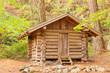 Old solid log cabin shelter hidden in the forest