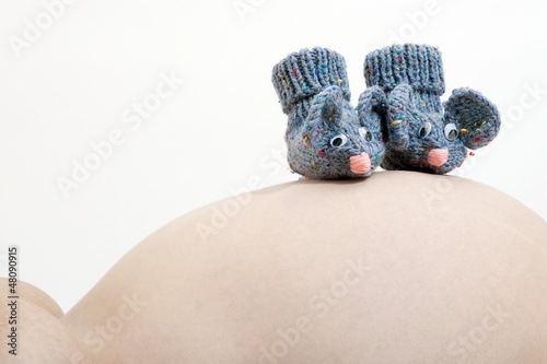 Cute little mouse booties on a pregnant belly