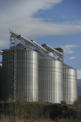 A row of shiny, steel silos