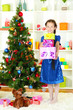 Little girl holding gift box near christmas tree