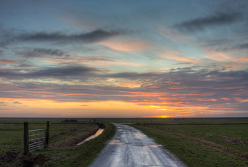 Country road towards horizon at sunrise