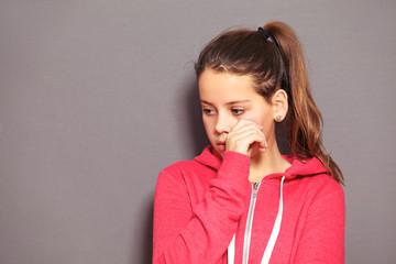 Sad little girl wiping away tears