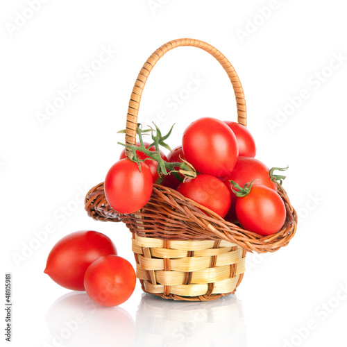 Cherry tomatoes in a basket, isolated on white
