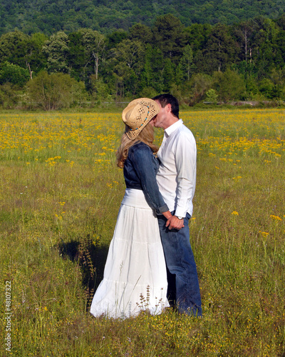 Embracing in field of yellow flowers