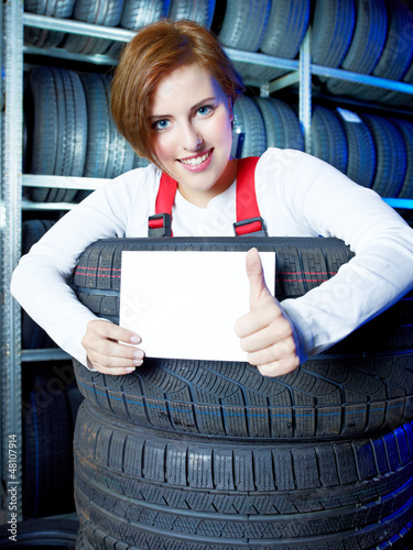 Apprentice showing thumb up for tire changing with blackboard