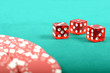 Poker gambling chips and few red dices on a green playing table