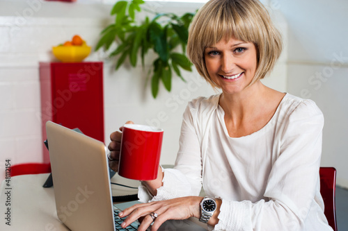 Cheerful woman holding coffee mug and working