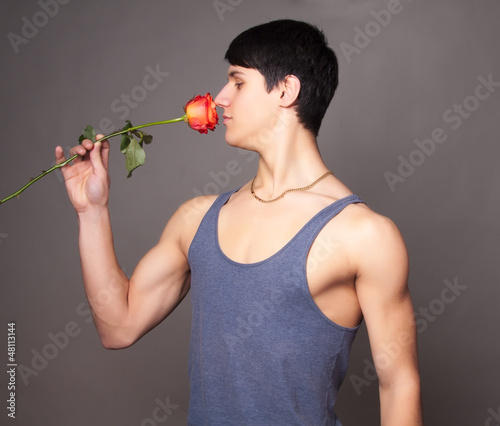 muscular man with a rose in hands