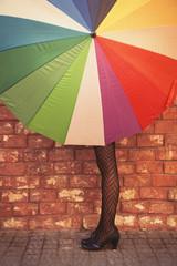 Fashionable woman hides behind an umbrella