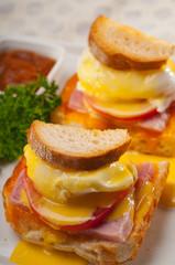 eggs benedict on bread with tomato and ham
