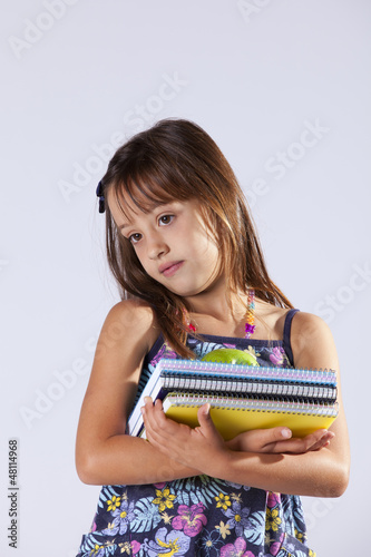 Little girl holding books and a apple