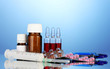 medical ampules, bottles, pills and syringes on blue background