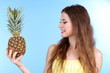 Beautiful woman with pineapple on blue background