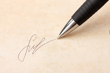 Closeup of signature (fake, not real) and pen, on old paper