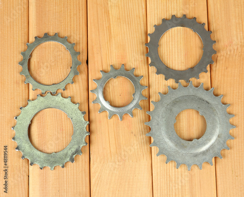 Metal cogwheels on wooden background