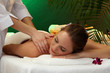 beautiful woman in spa salon with stones getting massage,