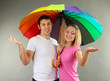Loving couple with umbrella on grey background