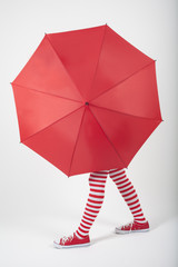 The girl standing behind a large red umbrella