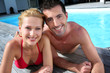 Cheerful couple laying on pool deck in front of house