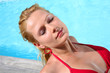 Blond woman in red bikini relaxing by pool