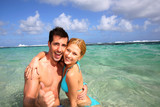 Couple in a caribbean lagoon showing thumbs up