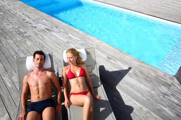Fancy couple relaxing in longchairs by swimming pool
