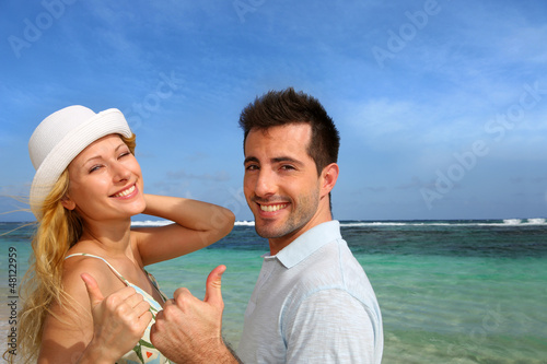Couple at the beach showing thumb up