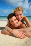 Cheerful young couple laying on a sandy beach