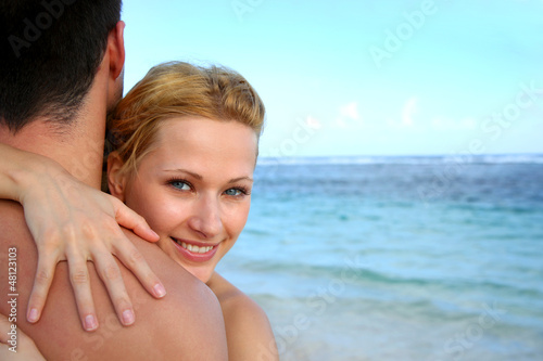 Beautiful girl embracing boyfriend at the beach