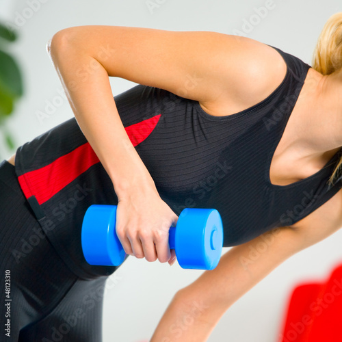 Young happy smiling woman with dumbbells, indoors