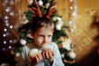 The boy with small horns of a deer under a New Year tree with be