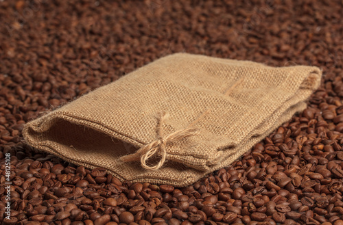 Coffee bag on coffee beans surface. Focused on bow.