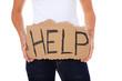 Weibliche Person hält Pappschild mit der Aufschrift help