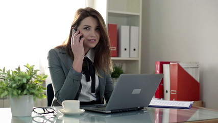 Young businesswoman with cellphone, laptop and documents