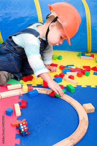 Kleiner Junge spielt mit Holzspielzeug