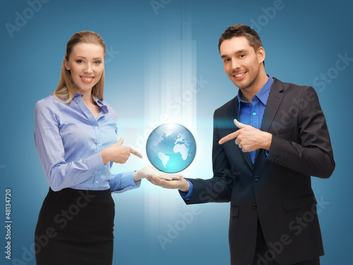 man and woman showing earth globe on the palms