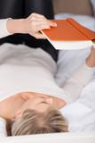entspannte frau liest ein buch im bett