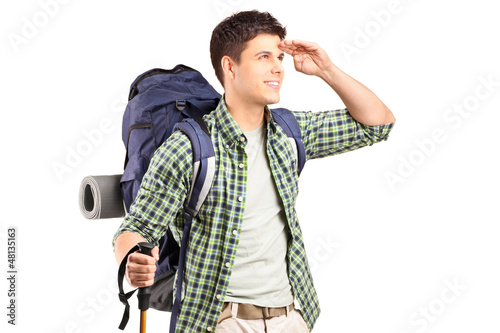 A hiker with backpack looking
