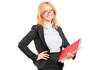 A smiling female teacher holding a notebook