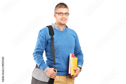 A smiling male student with shoulder bag holding notebooks
