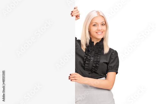 A smiling woman posing next to a blank panel