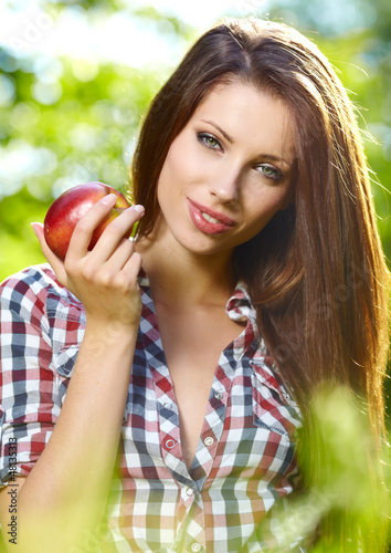 Portrait of beautifu young woman with a basket of fruit at summe