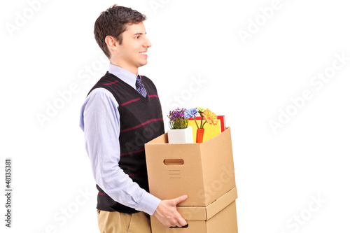 A smiling male walking with boxes moving into a new home