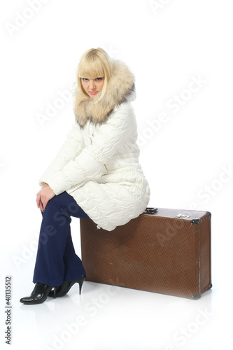 portrait of blonde girl in warm jacket with suitcase