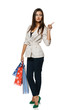 Full length of woman holding shopping bags and pointing to side