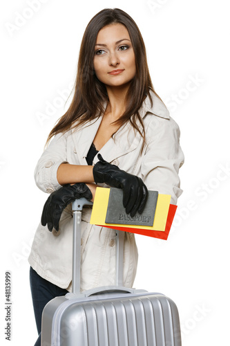 Female standing with travel bag, holding passport and tickets