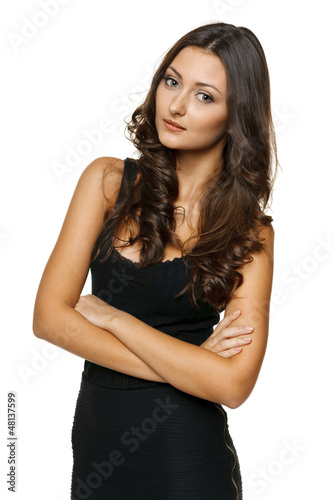 Beautiful young woman standing with folded hands