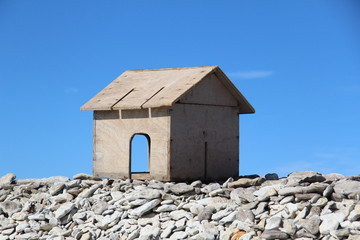 tiny wooden house against a blue sky background
