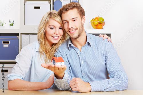 Paar trägt kleines Haus auf der Hand